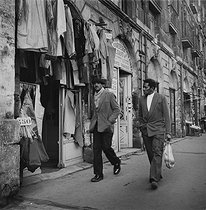 Roger-Viollet | 413493 | Immigrants walking in a shopping street. Photograph by Janine Niepce (1921-2007). | © Janine Niepce / Roger-Viollet