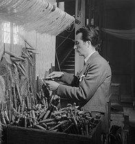 Roger-Viollet | 422273 | Weaver in front of his weaving loom at the Gobelins Manufactory. Paris, 1920-1950. | © Laure Albin Guillot / Roger-Viollet