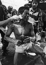 Roger-Viollet | 445538 | Wounded soldier treated by his comrades. Cambodia, 1975. | © Françoise Demulder / Roger-Viollet