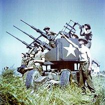 Roger-Viollet | 479418 | Guerre 1939-1945. Opération Overlord. Soldats de la 3ème division d'infanterie canadienne sur un canon antiaérien installé sur Juno Beach dans les environs de Bernières-sur-Mer (Calvados), 6 juin 1944. | © Bilderwelt / Roger-Viollet