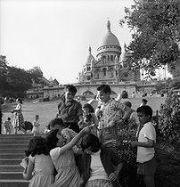 Roger-Viollet | 482899 | Group of children on the Butte Montmartre, under the Sacré-Coeur. Paris, 1956. Photograph by Janine Niepce (1921-2007). | © Janine Niepce / Roger-Viollet