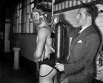 Roger-Viollet | 485012 | Georges Commeines, inventeur français, procédant à l'installation sur un expérimentateur de son appareil permettant de plonger jusqu'à 55 mètres. Paris, piscine Ledru-Rollin, février 1944. | © LAPI / Roger-Viollet