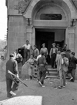 Roger-Viollet | 486562 | Spanish Civil War (1936-1939). Anarchists occupying a convent later turned into a canteen (Hélène Roger-Viollet among them). On the left, a man is hiding a notice  State property . Seo de Urgel (Catalonia), July 1936. | © Roger-Viollet / Roger-Viollet
