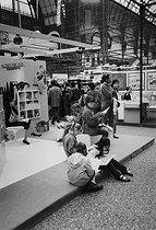 Roger-Viollet | 495027 | Children reading during a book fair at the Grand Palais. Paris (VIIIth arrondissement), April 1983. Photograph by Janine Niepce (1921-2007). | © Janine Niepce / Roger-Viollet