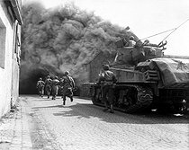 Roger-Viollet | 507006 | World War II. Soldiers of the 55th Armored infantry battalion and tank of the 22nd Tank Battalion, move through smoke filled street. Wernberg, Germany. April 22, 1945. | © US National Archives / Roger-Viollet