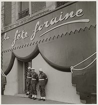 Roger-Viollet | 507608 | Three soldiers of the Military Police, standing guard, in front of the cabaret  la fête foraine , place Pigalle. Paris (IXth arrondissement), 1945. Photograph by Roger Schall (1904-1995). Paris, musée Carnavalet. | © Roger Schall / Musée Carnavalet / Roger-Viollet