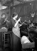 Roger-Viollet | 512305 | World War I. Women making helmets for the French army: molding visors. France, 1915. | © Jacques Boyer / Roger-Viollet