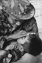 Roger-Viollet | 513225 | Vietnam War. Wounded child at the hospital with his father, he died a few days later. Saigon, 1975. The original caption said: 4/4, the death of a child.  Despair remains . | © Françoise Demulder / Roger-Viollet