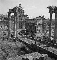 Roger-Viollet | 522774 | Après-guerre. Le Forum Romain avec les colonnes du pronaos du temple du divin Vespasien (dit également temple de Vespasien et Titus) construit entre 79 et 96 et l'Arc de Titus. Rome (Italie), vers 1950. | © Gaston Paris / Roger-Viollet