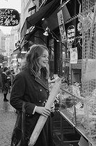 Roger-Viollet | 536443 | American student at the market, rue Mouffetard. Paris, circa 1970. Photograph by Janine Niepce (1921-2007). | © Janine Niepce / Roger-Viollet