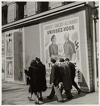 Roger-Viollet | 549686 | Propaganda poster for the compulsory work service (STO)  French and German workers, join forces , avenue des Champs-Elysées. Paris (VIIIth arrondissement), 1943. Photograph by Roger Schall (1904-1995). Paris, musée Carnavalet. | © Roger Schall / Musée Carnavalet / Roger-Viollet