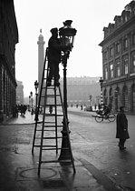 Roger-Viollet | 550688 | Cleaning street lamps on the place Vendôme. Paris (Ist arrondissement), 1944. | © LAPI / Roger-Viollet