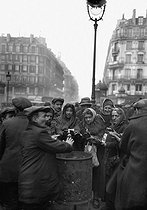 Roger-Viollet | 557169 | Paris. Tramps warming up around a brazier, around 1910. | © Albert Harlingue / Roger-Viollet