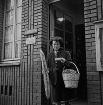 Roger-Viollet | 568603 | Workers' family life. Woman back in her council flat after the market. Paris, 1952. | © Jacques Rouchon / Roger-Viollet