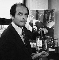 Roger-Viollet | 573714 | Jacques Polge (born in 1943), French perfumer, nose for Chanel, holding a bottle of Chanel N°5. Paris, April 1981. | © Kathleen Blumenfeld / Roger-Viollet