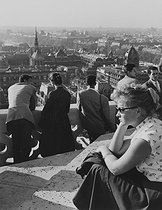 Roger-Viollet | 574778 | Young woman and visitors at the top of the left tower of Notre-Dame cathedral. Paris (IVth arrondissement), 1956. Photograph by Janine Niepce (1921-2007). | © Janine Niepce / Roger-Viollet
