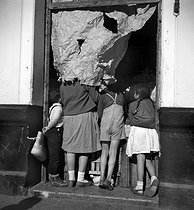 Roger-Viollet | 614027 | Children looking into a shop protected from the sun by some wrapping paper. Malaga (Spain), January 1957. Photograph by Hélène Roger-Viollet (1901-1985). | © Hélène Roger-Viollet / Roger-Viollet