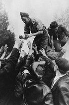 Roger-Viollet | 618747 | Guerre 1939-1945. Libération de Paris. Soldats alliés distribuant des cigarettes. | © Roger-Viollet / Roger-Viollet