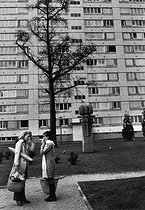 Roger-Viollet | 644425 | Two neighbours talking while coming back from the market. Paris suburbs, 1974. Photograph by Janine Niepce (1921-2007). | © Janine Niepce / Roger-Viollet