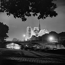 Roger-Viollet | 647203 | The Pont de l'Archevêché and Notre-Dame de Paris Cathedral illuminated. Paris (IVth arrondissement), 1965-1970. | © Ray Halin / Roger-Viollet