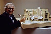 Roger-Viollet | 655692 | Frank Gehry (né en 1929), architecte américano-canadien, devant la maquette de l'American Center à Paris, inauguré en 1993, le bâtiment abrite la Cinémathèque française, la bibliothèque du Film et les Archives du film depuis 2005. Paris, 1989. | © Jean-Pierre Couderc / Roger-Viollet