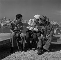 Roger-Viollet | 658674 | Jean-Victor Fischer (1904-1985), German-born French photographer, with two soldiers from the Fidel Castro's liberation army. Havana (Cuba), March 1959. Photograph by Hélène Roger-Viollet (1901-1985). | © Hélène Roger-Viollet / Roger-Viollet