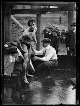 Roger-Viollet | 676925 | World War I. Swimmer getting prepared before the Swimming across Paris, swimming race taking place between the Pont National and the Pont Mirabeau. Paris, on July 29, 1917. | © Excelsior - L'Equipe / Roger-Viollet