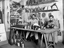 Roger-Viollet | 678820 | Fabrication d'accessoires de cotillons. Peinture de casques militaires pour enfants. France, 1908. | © Jacques Boyer / Roger-Viollet