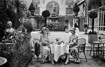 Roger-Viollet | 685852 | Women's fashion. Ladies drinking some tea in the garden of the Ritz Hotel. Paris (Ist arrondissement), 1930. | © Boris Lipnitzki / Roger-Viollet