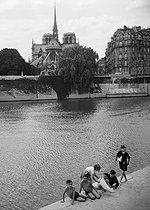 Roger-Viollet   704877   Children bathing in the river Seine in front of the Notre-Dame de Paris Cathedral. Paris, 1956. Photograph by Janine Niepce (1921-2007).   © Janine Niepce / Roger-Viollet