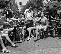 Roger-Viollet | 705638 | Chorus girls at the terrace of the  Fouquet's . Paris (VIIIth arrondissement), avenue des Champs-Elysées, on June 26, 1952. | © Roger-Viollet / Roger-Viollet
