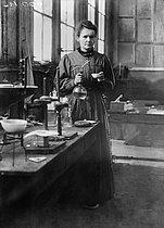 Roger-Viollet | 710255 | Marie Curie (1867-1934), physicienne française, dans son premier laboratoire installé dans un hangar de l'EPCI, rue Lhomond, Paris (Vème arr.), 1896-1905. | © Albert Harlingue / Roger-Viollet