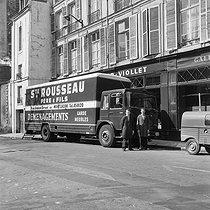 Roger-Viollet | 733587 | Déménagement : arrivée de l'agence LAPI, rue de Seine. En arrière-plan, vitrine de l'agence Roger-Viollet. Paris (VIème arr.), avril 1976. | © Collection Roger-Viollet / Roger-Viollet
