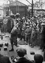 Roger-Viollet | 743964 | Strongman lifting up dumbbells. Paris, about 1925. | © Roger-Viollet / Roger-Viollet