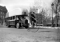 Roger-Viollet | 753732 | World War II. Traffic in Paris. A Penny-farthing and a gas bus, March 1941. | © LAPI / Roger-Viollet