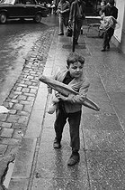 Roger-Viollet | 756384 | Young boy carrying a French stick. Algiers (Algeria), 1967. Photograph by Jean Marquis (1926-2019). | © Jean Marquis / Roger-Viollet