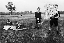 Roger-Viollet | 775919 | Young boys playing with kites made of banknotes devalued during the Weimar Republic. Germany, circa 1930. | © Albert Harlingue / Roger-Viollet