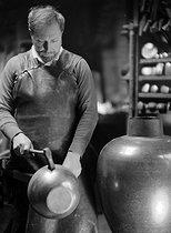 Roger-Viollet | 779254 | Jean Dunand (1877-1942), Swiss sculptor, copperware manufacturer and decorator on lac, beating a vase. | © Laure Albin Guillot / Roger-Viollet