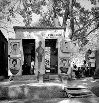 Roger-Viollet | 784014 | Barber and hairdresser. Bobo-Dioulasso (French Upper Volta, present Burkina Faso), February 1963. Photograph by Hélène Roger-Viollet (1901-1985). | © Hélène Roger-Viollet / Roger-Viollet