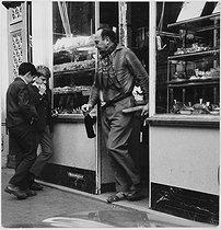 Roger-Viollet | 785580 | Man leaving a bakery. Paris, 1960's. Photograph by Janine Niepce (1921-2007). | © Janine Niepce / Roger-Viollet