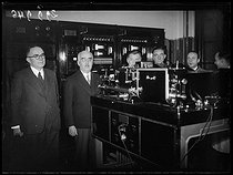 Roger-Viollet | 796045 | Édouard Belin and Mr. Picault, director of the telephotographic service (T.S.F.) at the reception of a photograph of Mr. Le Beau, general governor of Algeria, and the transmission to Algiers to the Minister of  Postes, Télégraphes et Téléphones  (P.T.T.), during the inauguration ceremony of the wiretelephotographic line between Paris and Algiers at the Ministry of the P.T.T., engineered by Édouard Belin (1876-1963), French engineer, inventor of the wirephoto, remotely transmission system for photographs. Paris, janvier 1939. Photographie du journal  Excelsior . | © Excelsior - L'Equipe / Roger-Viollet