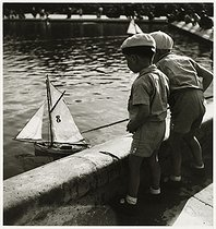 Roger-Viollet | 806045 | Two children playing with a boat in the pond of the Tuileries Garden. Paris (Ist arrondissement), 1938. Photograph by Roger Schall (1904-1995). Paris, musée Carnavalet. | © Roger Schall / Musée Carnavalet / Roger-Viollet
