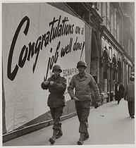 Roger-Viollet | 811699 | US soldiers in front of a poster  Congratulations on a job well done , rue de la Paix. Paris (IInd arrondissement), 1945. Photograph by Roger Schall (1904-1995). Paris, musée Carnavalet. | © Roger Schall / Musée Carnavalet / Roger-Viollet