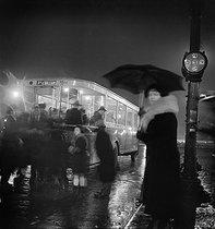 Roger-Viollet   835095   Un arrêt d'autobus, la nuit sous la pluie, autobus en direction de la porte d'Orléans, Paris. 1937. Photographie de Roger Schall (1904-1995).   © Roger Schall / Roger-Viollet