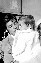 Roger-Viollet | 835639 | Alain Delon (born in 1935), French actor, with his son Anthony for his christening, on May 1st, 1966. Photograph by Georges Kelaïditès (1932-2015). | © Georges Kelaïditès / Roger-Viollet
