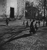 Roger-Viollet | 861686 | Children playing soccer in front of the Santa Maria of Alhambra church. Granada (Spain), January 1957. Photograph by Hélène Roger-Viollet (1901-1985). | © Hélène Roger-Viollet / Roger-Viollet