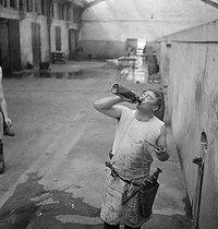 Roger-Viollet | 862095 | Butcher drinking at the Vaugirard slaughterhouse. Paris, 1950. | © Gaston Paris / Roger-Viollet