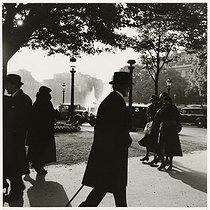 Roger-Viollet | 863974 | Passers-by at the roundabout of the Champs-Elysées. Paris (VIIIth arrondissement), 1937. Photograph by Roger Schall (1904-1995). Paris, musée Carnavalet. | © Roger Schall / Musée Carnavalet / Roger-Viollet