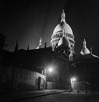 Roger-Viollet | 868191 | Montmartre district. The illuminated Sacré-Coeur basilica. Paris (XVIIIth arrondissement), circa 1940. | © Gaston Paris / Roger-Viollet