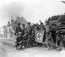 Roger-Viollet | 882312 | World War II. Lined up in front of a wrecked German tank and displaying a captured swastika, is a group of Yank infantrymen who were left behind to  mop-up  in Chambois, France, last stronghold of the Nazis in the Falaise gap area. August 20, 1944. | © US National Archives / Roger-Viollet